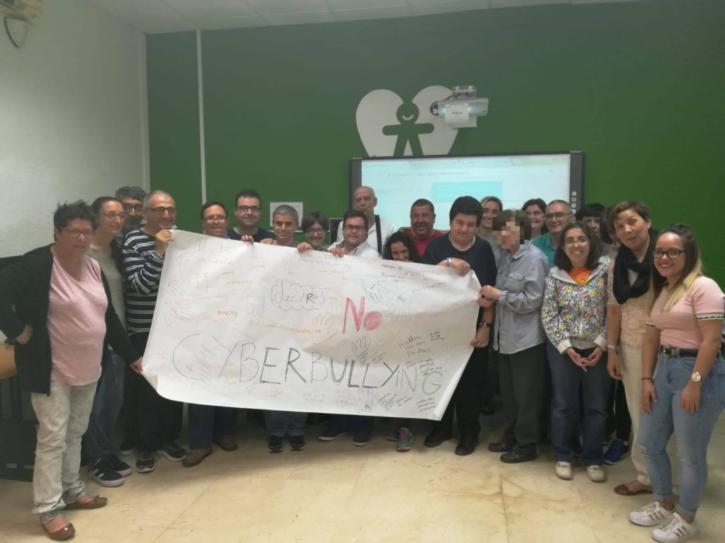 """Imagen de participantes de la charla dirigida a socios y socias de la entidad mostrando la pancarta que realizaron con el texto central de """"NO, al cyberbullying"""""""