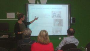 Imagen de la psicóloga Lucia Castroverde impartiendo la charla con el apoyo audiovisual de una presentación multimedia.