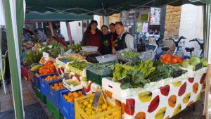 Imagen de 3 integrantes de la alquería durante en el puesto de un mercado con sus verduras y frutas ecológicas