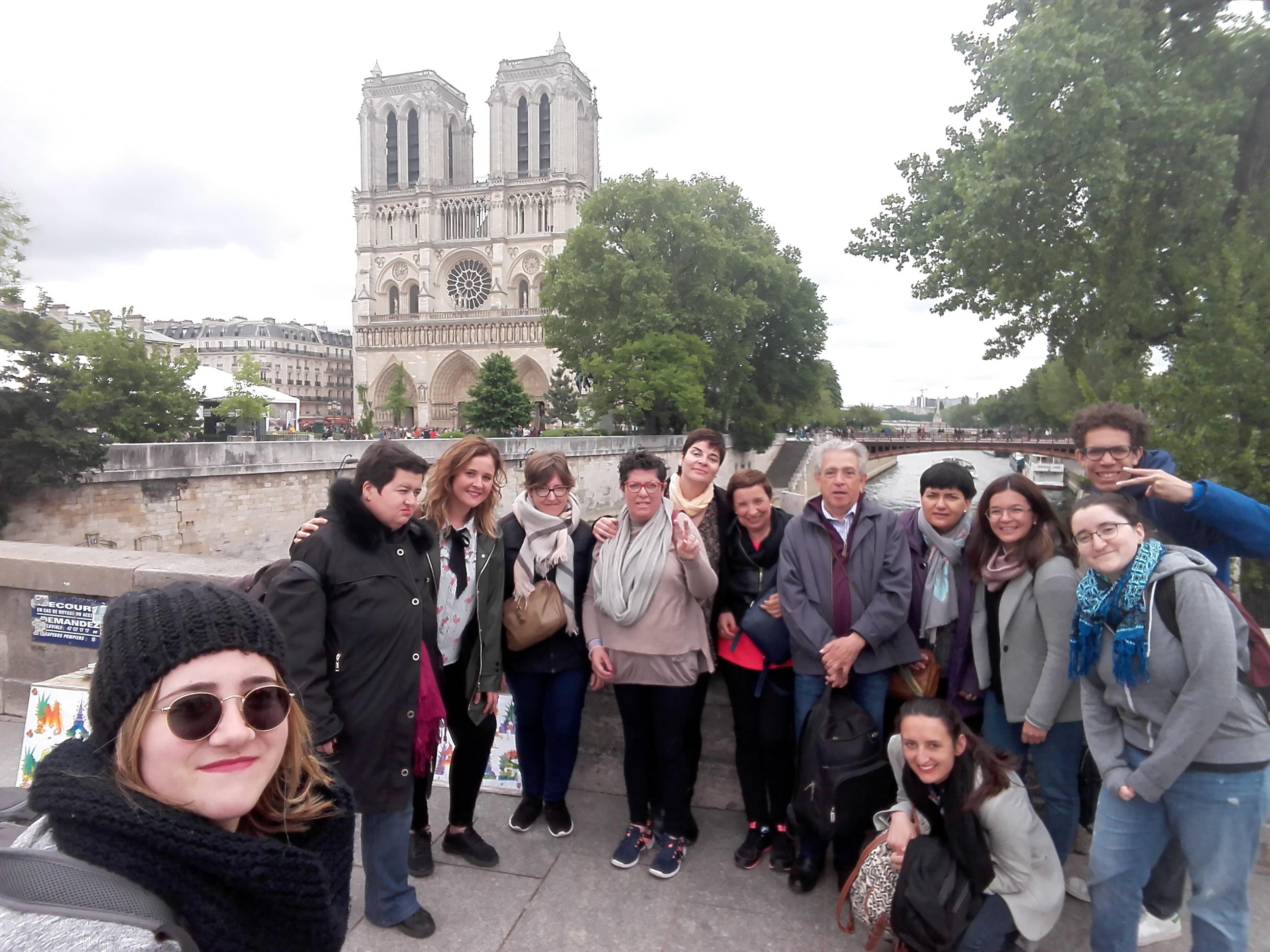 La vivienda tutelada de mujeres posa sonrientes frente a la catedral de Notre Dame en Paris junto con los miembros de la asociación Espaces Ouverts