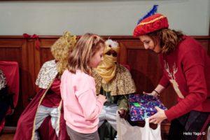 Niña recogiendo junto a los reyes magos en la fiesta de reyes de la asociación Amigos de la calle.