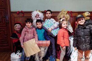 niños y niñas junto a los reyes magos en la fiesta de reyes de la asociación Amigos de la calle.